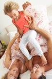 Семья ослабляя совместно в кровати Стоковые Изображения