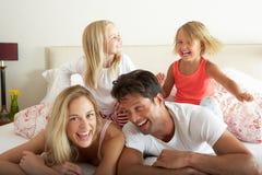 Семья ослабляя совместно в кровати Стоковая Фотография RF