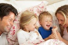 Семья ослабляя совместно в кровати Стоковые Фото