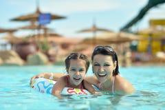 Семья ослабляет в бассейне Стоковое Изображение