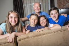 Семья ослабляя внутри помещения смотрящ телевидение совместно Стоковое фото RF