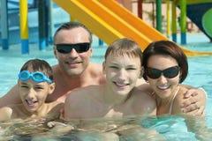 Семья ослабляя в бассейне Стоковое Изображение
