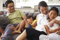 Семья ослабляя на софе дома совместно стоковое фото