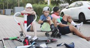 Семья отдыхает после прогулки на роликах и скутере акции видеоматериалы