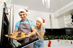 Семья печет пирожные на рождестве в кухне Стоковые Изображения RF