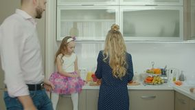 Семья подготавливая завтрак совместно в кухне акции видеоматериалы