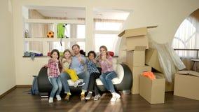 Семья показывая большие пальцы руки вверх внутри помещения