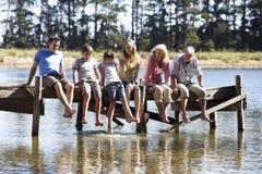 Семья 3 поколений сидя на деревянной моле рассматривая вне озеро Стоковое фото RF
