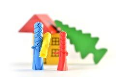 Семья покрашенных штепсельных вилок и поврежденного дома стоковая фотография rf