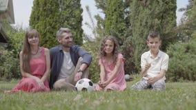 Семья портрета счастливая сидя на траве в саде совместно Мать, отец, сын, и дочь смотря в акции видеоматериалы
