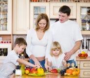 Семья подготавливая салат стоковые изображения