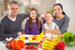 Семья подготовляя еду Время принятия пищи совместно дома Стоковая Фотография