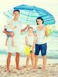 Семья под зонтиком солнца на пляже Стоковое Изображение RF