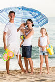 Семья под зонтиком солнца на пляже Стоковые Изображения