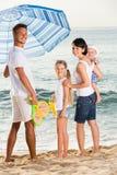 Семья под зонтиком солнца на пляже Стоковые Изображения RF