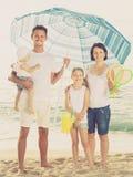 Семья под зонтиком солнца на пляже Стоковое Изображение