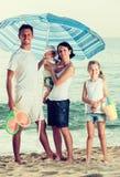 Семья под зонтиком солнца на пляже Стоковая Фотография