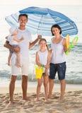Семья под зонтиком солнца на пляже Стоковая Фотография RF