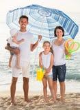 Семья под зонтиком солнца на пляже Стоковое фото RF