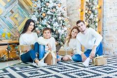 Семья празднуя дома отец, мать и дети на предпосылке рождественской елки с настоящими моментами сидят на Стоковые Изображения RF