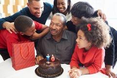 Семья празднуя семидесятый день рождения совместно стоковое изображение