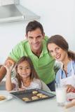 Семья представляя в кухне с домодельными печеньями Стоковая Фотография RF