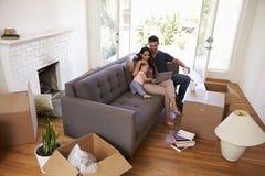 Семья принимает пролом на софе используя компьтер-книжку на Moving день Стоковое Изображение RF