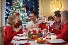 Семья при дети имея рождественский ужин на дереве стоковые изображения rf