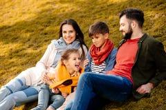 Семья при 2 дет ослабляя на травянистой лужайке Стоковые Фотографии RF