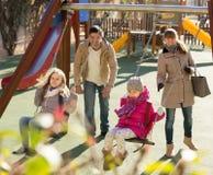 Семья при 2 девушки имея потеху на качаниях outdoors Стоковая Фотография