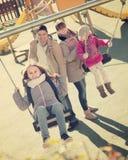 Семья при 2 девушки имея потеху на качаниях outdoors Стоковое Фото