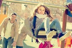 Семья при 2 девушки имея потеху на качаниях outdoors Стоковая Фотография RF