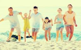 Семья при дети бежать совместно на пляже Стоковая Фотография