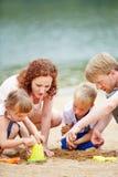 Семья при дети играя на пляже Стоковые Изображения
