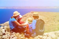 Семья при дети смотря карту в горах Стоковые Изображения RF