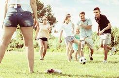 Семья при 4 дет бежать после шарика Стоковое Изображение