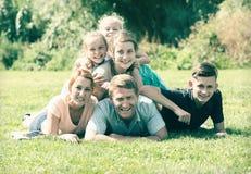Семья при 4 дет лежа в парке Стоковые Фото
