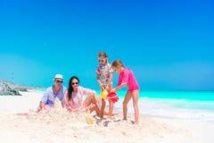 Семья при 2 дет делая песок рокирует на тропическом пляже Стоковые Фотографии RF