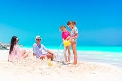 Семья при 2 дет делая песок рокирует на тропическом пляже Стоковое Изображение