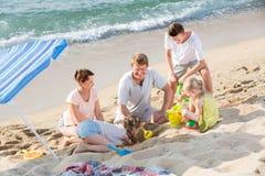 Семья при 4 дет играя на пляже Стоковая Фотография RF