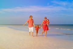 Семья при 2 дет имея потеху на пляже Стоковые Фотографии RF