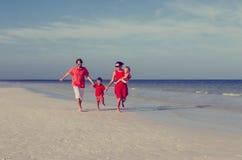 Семья при 2 дет имея потеху на пляже Стоковые Изображения RF