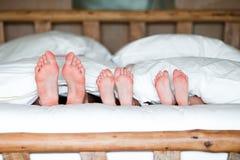Семья при 2 дет кладя в кровать с их ногами вперед Стоковое фото RF