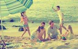 Семья при 4 дет ослабляя на пляже Стоковая Фотография