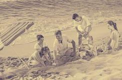 Семья при 4 дет ослабляя на пляже Стоковые Изображения