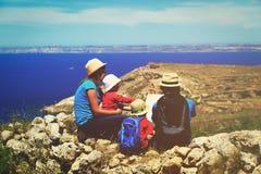 Семья при 2 дет смотря карту в горах, концепцию перемещения Стоковые Фото