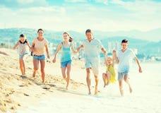 Семья при 4 дет счастливо бежать на пляже Стоковые Фотографии RF