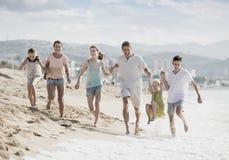 Семья при 4 дет счастливо бежать на пляже Стоковое Изображение