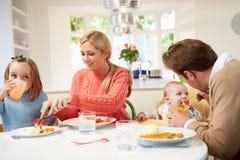 Семья при молодой младенец есть еду дома Стоковая Фотография