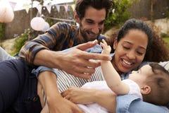 Семья при младенец играя на половике в саде совместно Стоковые Изображения